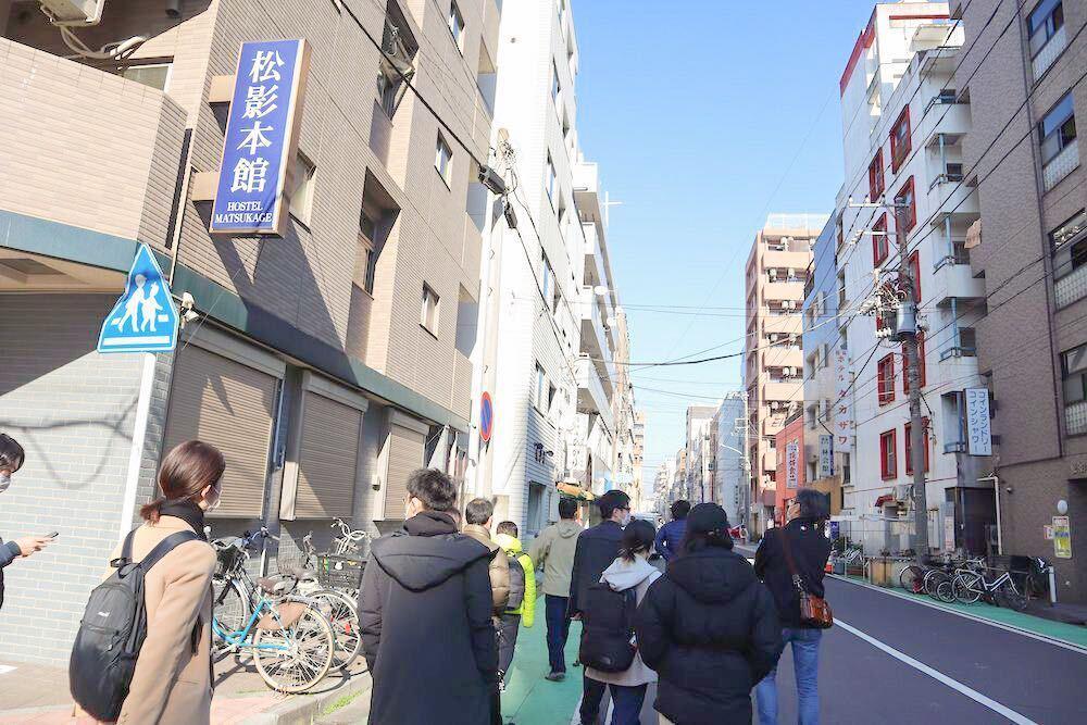 寿町の街を十数人が列になって歩く様子