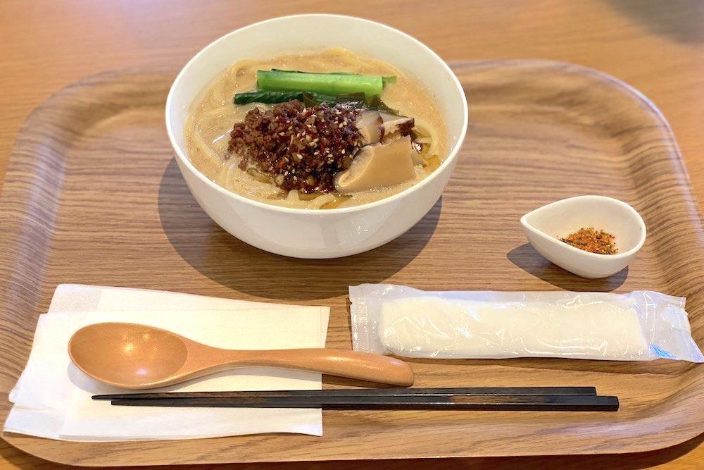 お盆の上に乗った横浜ヴィーガンラーメン。白濁色のスープに小松菜や肉味噌が乗っている。